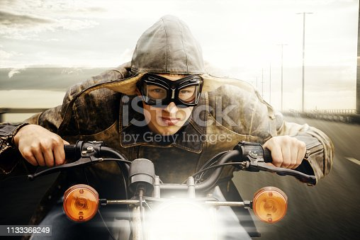 Young man with hat and goggles vintage look driving on a road