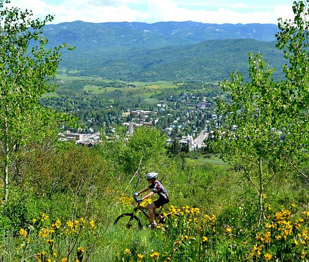 Young Mountain Biker Above Town A young mountain biker rides the trail above the town of Steamboat Springs, Colorado. steamboat springs stock pictures, royalty-free photos & images
