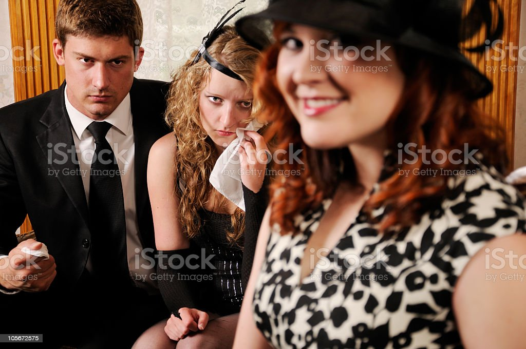 Young Mourners at Funeral Parlor Expressing Anger Hatred & Greed stock photo