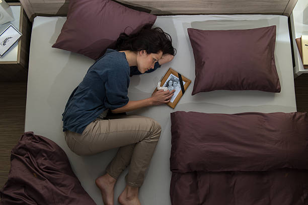 Young mourning woman lying in bed Young mourning woman lying in bed alone mourner stock pictures, royalty-free photos & images