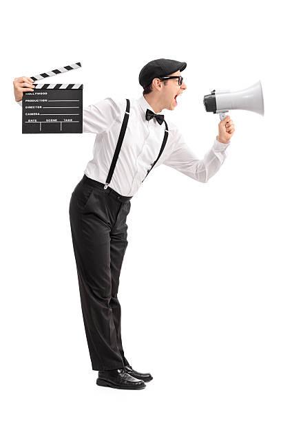 junge film director rufen auf megafon - klappe hut stock-fotos und bilder