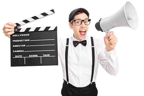 junge film director sprechen auf megafon - klappe hut stock-fotos und bilder