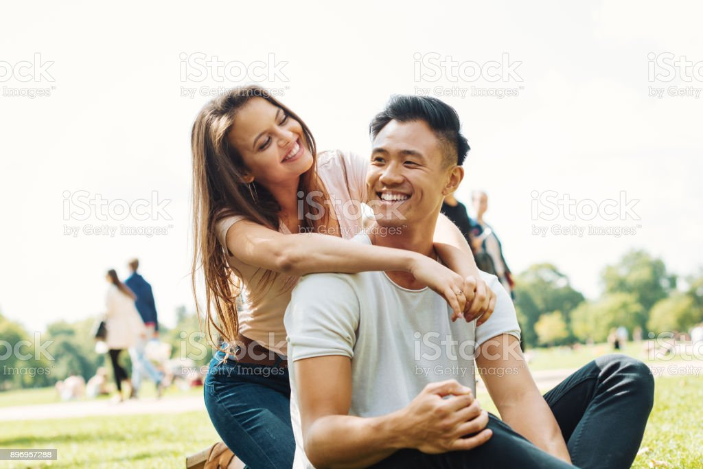 Young multi ethnic couple hugging in park stock photo
