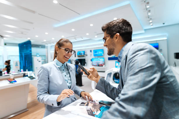 young multicultural couple looking for new smart phone to buy. woman looking at catalog while man holding smart phone. - store imagens e fotografias de stock