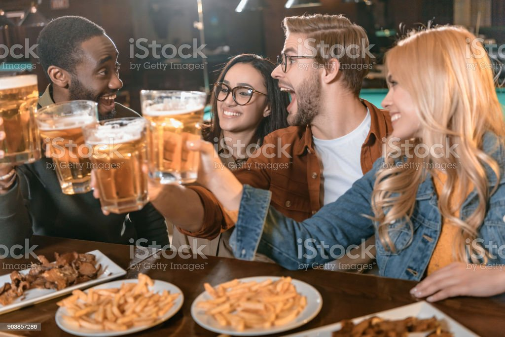 young multiculture company eating and drinking at bar - Royalty-free Adult Stock Photo