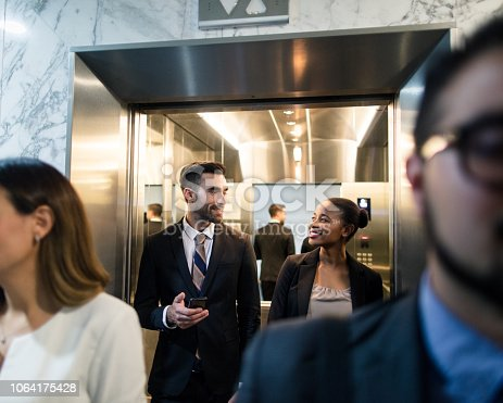 A multi-ethnic team of business executives walking out of an elevator in a business center