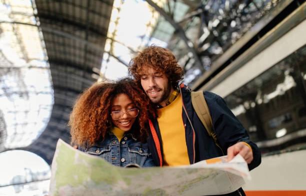 Young multi-ethnic couple checking map on train platform at station stock photo
