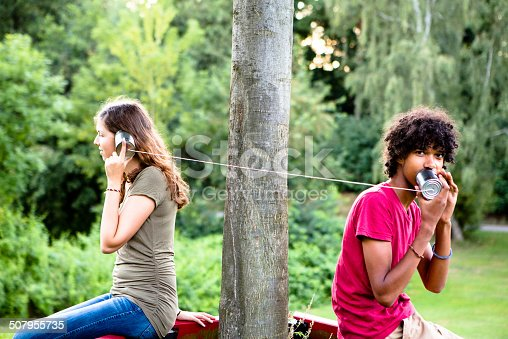 young multi-ethnic couple communicate with a tin can phone in the park, back lit