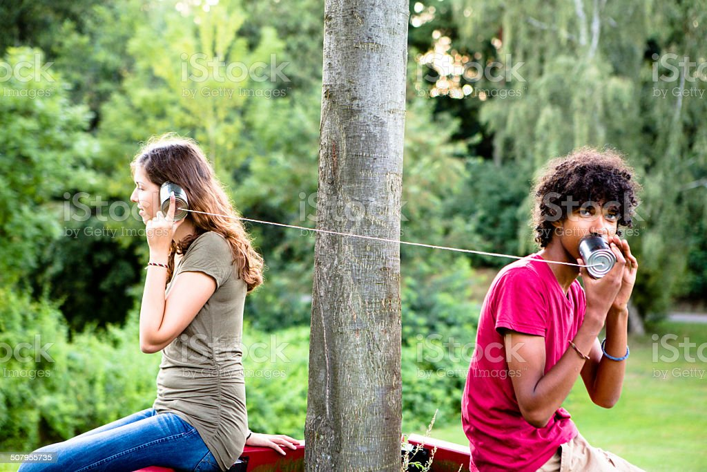 young multi-ethnic couple communicate with a tin can phone stock photo