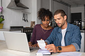 istock Young multiethnic couple examining home finance 1158243057
