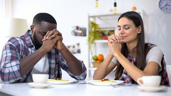 istock Young multiethnic couple praying before lunch, thanking God for meal, religion 1159251952