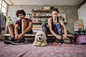 Young multi-ethnic couple sitting on bed at apartment and preparing for jogging, fluffy dog sitting near them