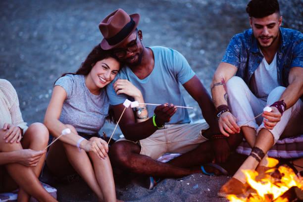 multi-ethnischen brautpaar vorbereitung smores am strand mit freunden - kochinsel stock-fotos und bilder