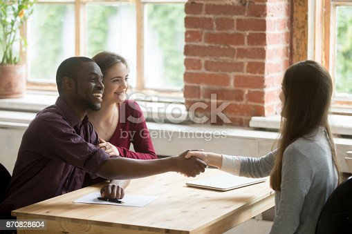 istock Young multiethnic couple shaking hands with real estate agent. 870828604