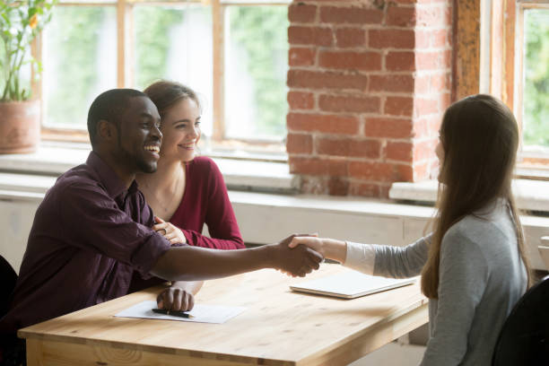 Young multiethnic couple shaking hands with real estate agent. stock photo