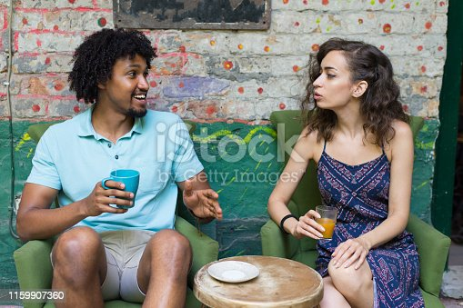 Young multi-ethnic couple talking in the cafe and drinking juice and tea.