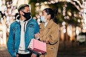 冬の病気予防のための保護フェイスマスクを着用しながら、市内のショッピングバッグを持って通りを歩く若い多民族カップル