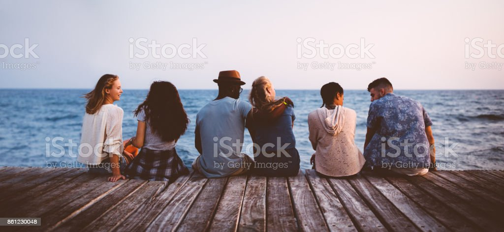 Young multi-ethnic couples and friends sitting on wooden jetty together stock photo