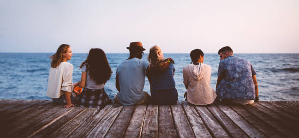 Young multi-ethnic couples and friends sitting on wooden jetty together - foto stock