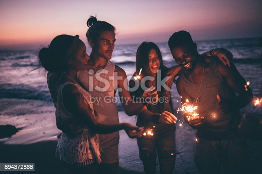 istock Young multi-ethnic couples celebrating with sparklers at beach after sunset 894372868