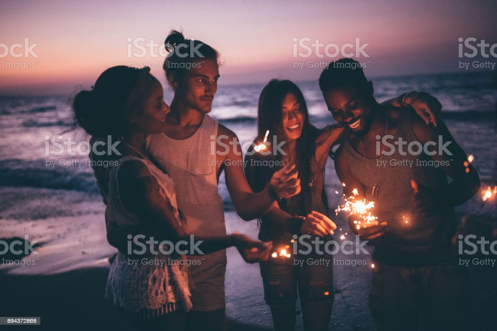 Young multi-ethnic couples celebrating with sparklers at beach after sunset stock photo