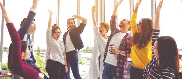 Young multiethnic diverse creative asian group huddle and high five hands together in office workshop with success or empower expression in teamwork. Young asian marketing team with copy space. stock photo