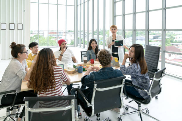 young multiethnic diverse creative asian group talking or brainstorm in office meeting workshop with technology. happy young student asian or college marketing team spend coffee break time together. - training imagens e fotografias de stock