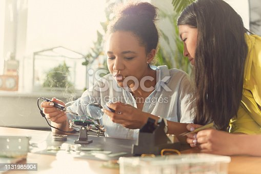 Two young women working on a device prototype. Soldering and checking voltage