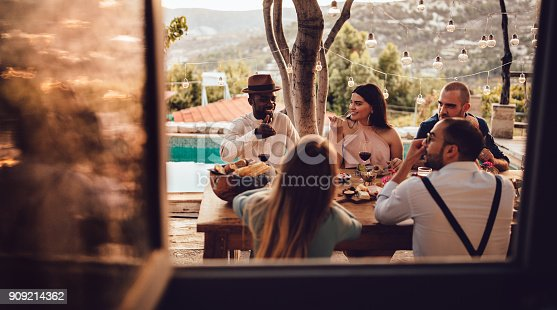 Young multi-ethnic friends having fun eating and drinking at rustic mediterranean village countryside cottage restaurant