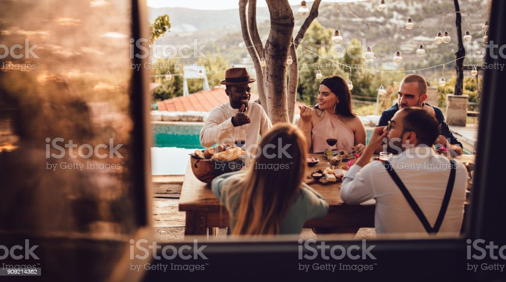 Young multi-ethnic friends and couples having lunch at village house stock photo