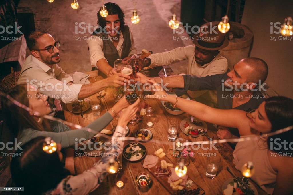 Young multi-ethnic friends celebrating and toasting at rustic dinner party stock photo