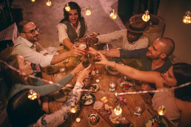 multi-ethnischen jugendliche feiern und bei rustikalen abendessen toasten - französische land tisch stock-fotos und bilder