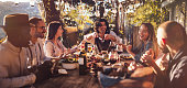 istock Young multi-ethnic friends dining at rustic countryside restaurant at sunset 903783156