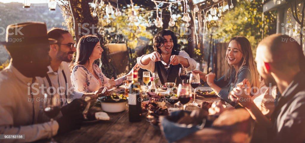Jovens amigos multi-étnica de refeições no restaurante rústico campestre ao pôr do sol - foto de acervo