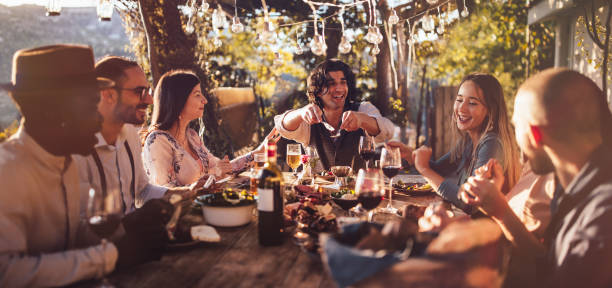 Young multi-ethnic friends dining at rustic countryside restaurant at sunset stock photo