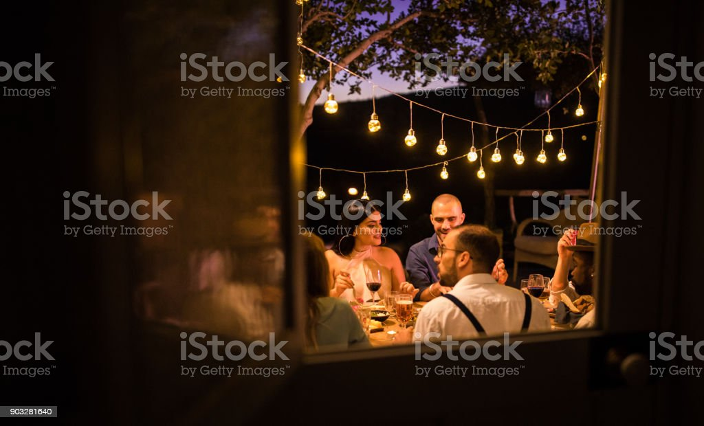 Young multi-ethnic friends having rustic dinner party in countryside stock photo