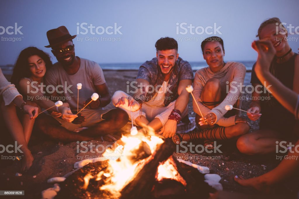 Young multi-ethnic friends roasting marshmallows on sticks at the beach stock photo