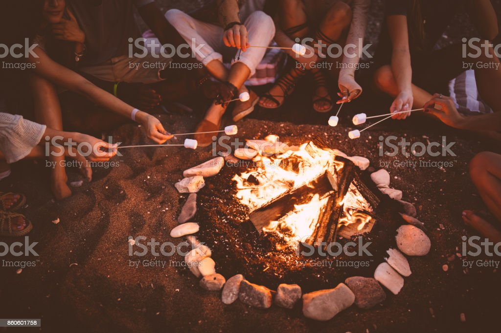 Young multi-ethnic friends roasting marshmallows over campfire at beach party stock photo