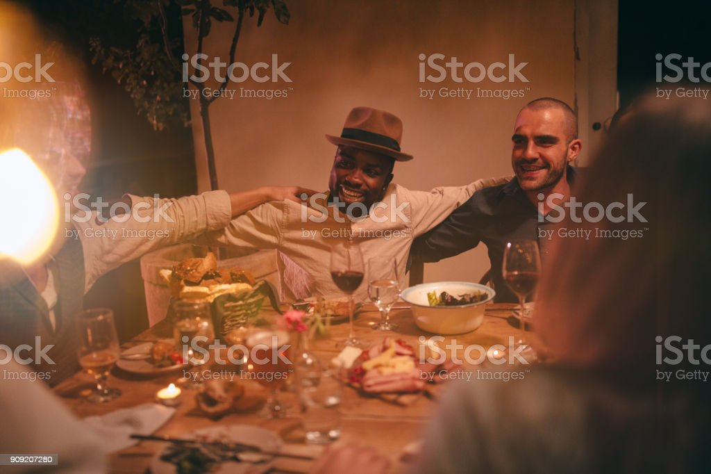 Young multi-ethnic friends singing and celebrating at rustic dinner party stock photo