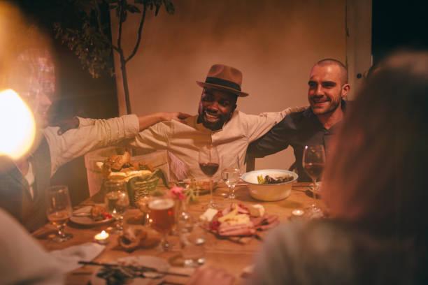 junge multi-ethnischen freunde singen und feiern im rustikalen dinner-party - französische land tisch stock-fotos und bilder