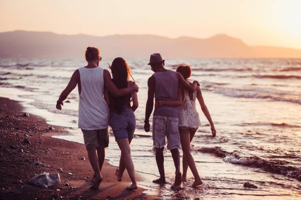 junge multi-ethnischen hipster paare zu fuß am strand bei sonnenuntergang - hochzeitsreise zypern stock-fotos und bilder