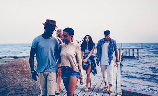 Young multi-ethnic hipster friends and couples walking on jetty