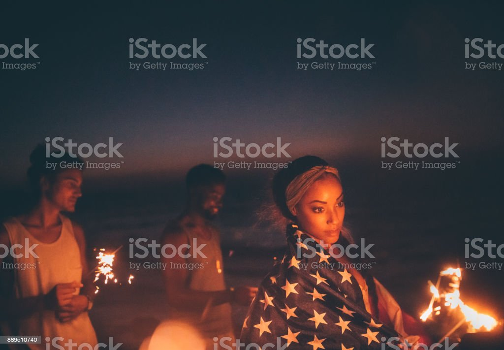 Young multi-ethnic hipster friends celebrating fourth of July with sparklers stock photo
