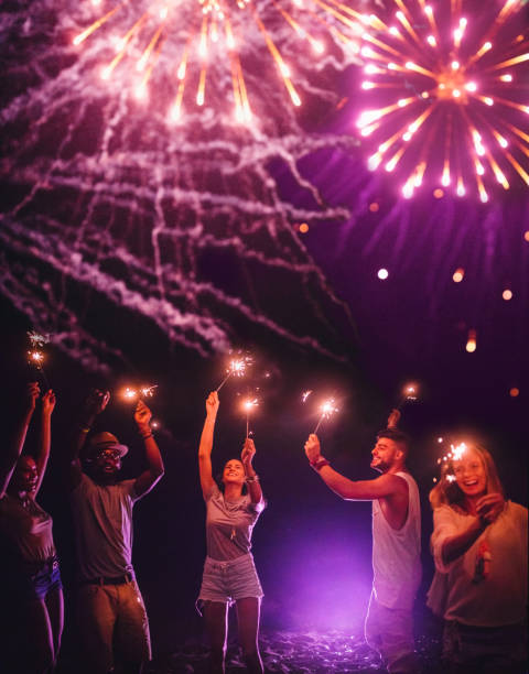 Young multi-ethnic hipster friends celebrating with sparklers and fireworks display stock photo