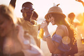 Young multi-ethnic hipster friends dancing at summer beach party