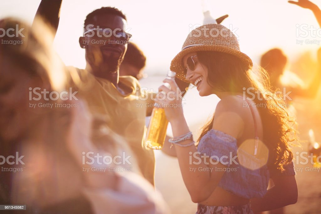 Young multi-ethnic hipster friends dancing at summer beach party stock photo
