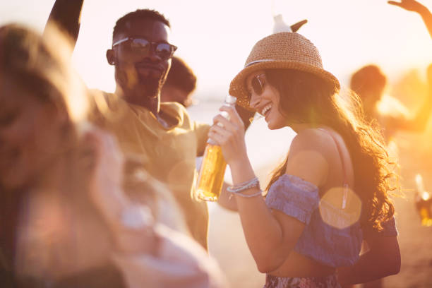 young multi-ethnic hipster friends dancing at summer beach party - beer alcohol stock pictures, royalty-free photos & images