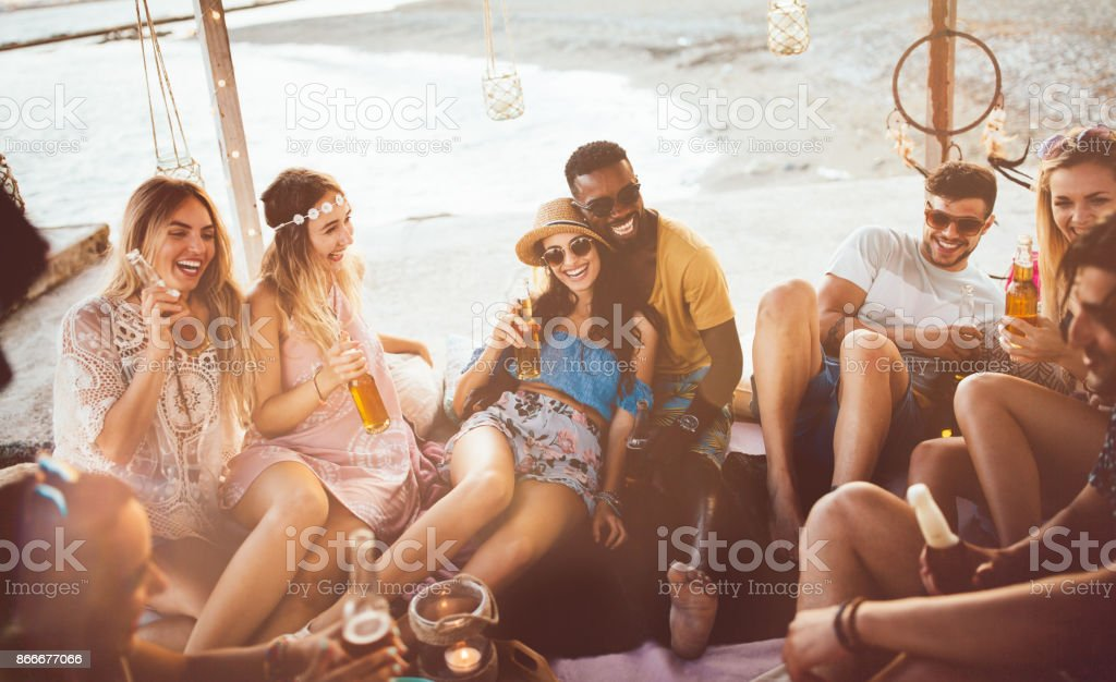 Young multi-ethnic hipster friends drinking beer at summer beach party stock photo