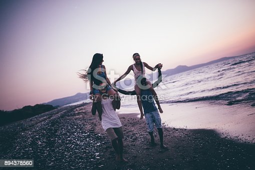 istock Young multi-ethnic hipster friends having fun with beach piggy-back rides 894378560