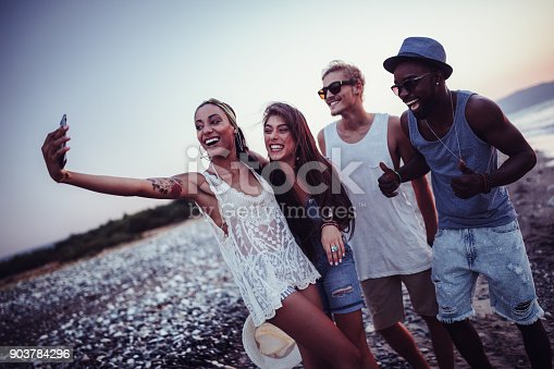 istock Young multi-ethnic hipster friends taking selfies at beach party 903784296